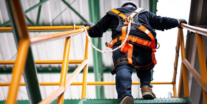 man in harness walking up to roof