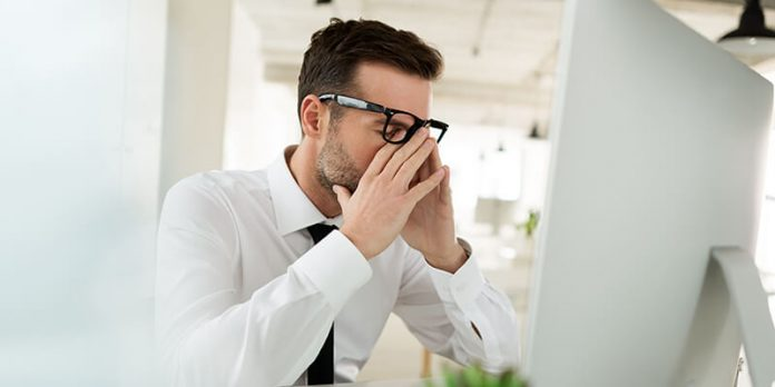 stressed man at computer - impact of materials shortages on contractors